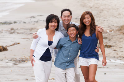 This photograph features an Asian family having casual family photos on the beach near The Montage Hotel in Laguna Beach. The family is wearing color coordinated outfits.